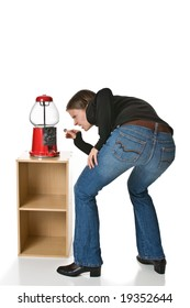 Confused or angry young woman in blue jeans tries to put a quarter into an empty gumball machine.