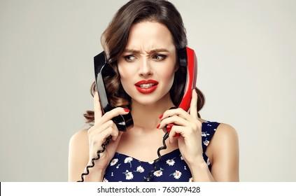 Confused annoyed woman with two old fashioned telephone.  Irritation, distrust and misunderstanding.