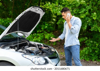 Confused arab guy driver looking under car hood, calling auto service, upset middle-eastern young man got stuck at highway, having phone conversation with friends, asking for help, side view