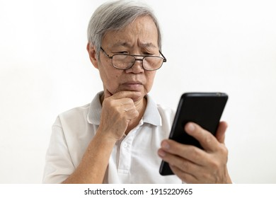 Confused asian senior woman with puzzled looks holding smartphone,confusing by information while using mobile phone or unable to understand,complex technology problems difficult to use for the elderly
