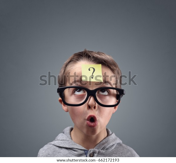 Confused boy thinking with question mark on sticky note on forehead