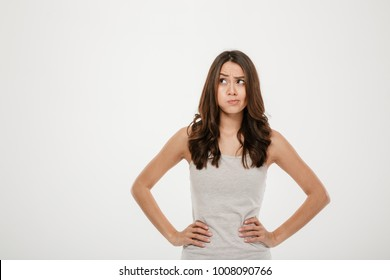 Confused brunette woman with arms on hips looking away over gray background