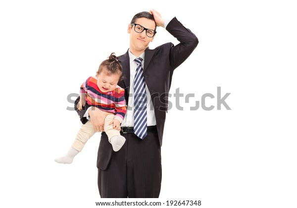 Confused businessman holding a crying baby isolated on white background