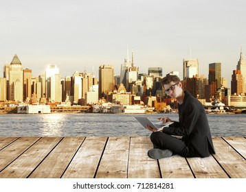 Confused businessman with laptop sitting on wooden pier with city view. Research concept