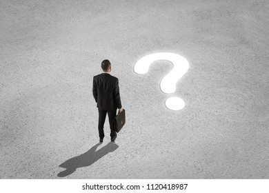Confused businessman looking at question mark on the floor