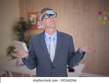 Confused businessman with sticky notes stuck on his forehead at office