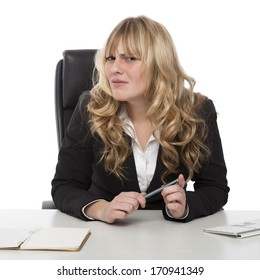 Confused businesswoman with a puzzled frown peering sideways at the camera as she tries to make sense of something or understand a colleague
