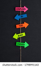 Confused by too many choices concept of colored arrows on black background.