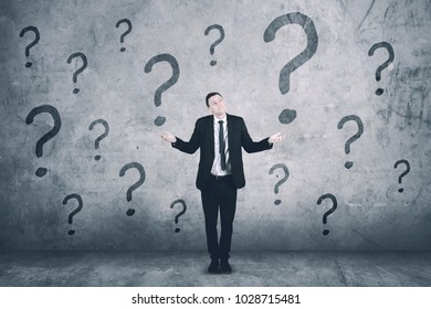 Confused caucasian businessman with question marks on the wall