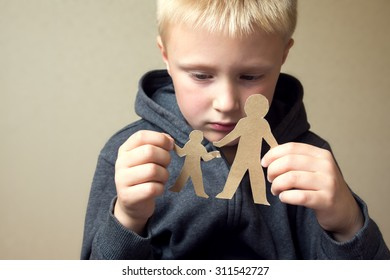 Confused child with cutting paper father and son, family problems, divorce, custody battle, suffer concept