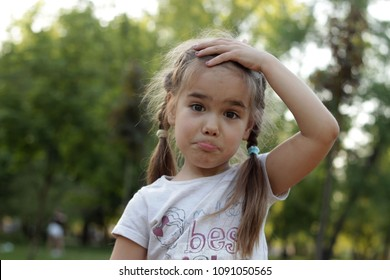 A confused closeup facial expression of a Caucasian pretty 5 years old girl, afraid of mistake, emotional child portrait, summer outdoor