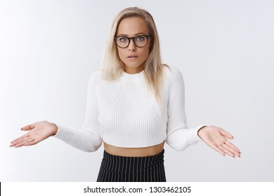 Confused clueless worried female assistant in glasses cropped sweater and skirt shrugging with hands sideways open mouth in confusion and frustration standing unaware and clueless over white wall