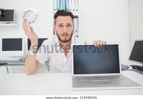 Confused computer engineer looking at camera with laptop in his office