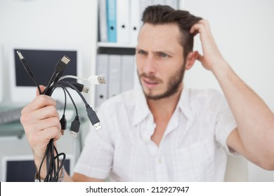 Confused computer engineer looking at wires in his office