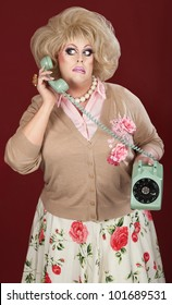Confused drag queen on phone call over maroon background