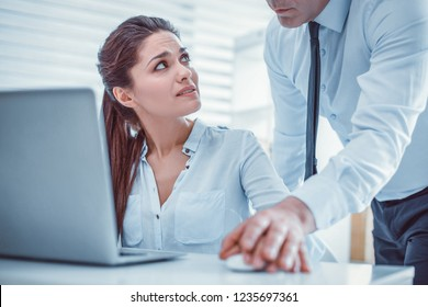 Confused female secretary. Young woman irritably asking her unprofessional coworker about his shameless behavior
