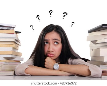 Confused female student laying between stacks of books, looking up with many question on her head, over white background