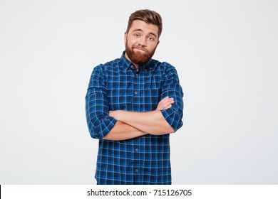 Confused frustrated bearded man standing with arms folded isolated over white background