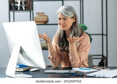Confused gray-haired mature lady, business woman manager or consultant, looking at the computer in confusion, received an incomprehensible message, or strange news