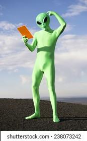 Confused green alien scratching head looking down at orange tablet