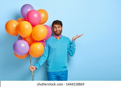 Confused hesitant male holiday maker raises palm with puzzlement, tries to make decision, holds multicolored bunch of air balloons, doesnt know whether all guests has come, wears blue clothes