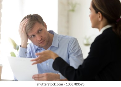 Confused hr manager and job candidature sitting at negotiation room, company representative hold head with hand looking at deceitful female feels perplexed. Unsuccessful passing of interview concept