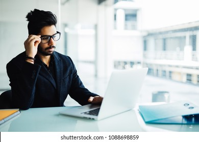 Confused indian businessman working on laptop in office