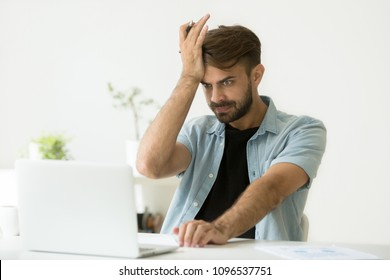 Confused irritated funny young man stressed about performing mistake while preparing annual financial report. Frustrated male student realizing notion getting ready for exam, writing down data.