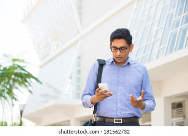 confused looking indian business male on a smartphone with office background