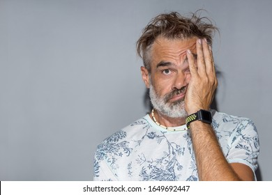 Confused man with funny messy hair. Indoor portrait of handsome man with grey beard and hair