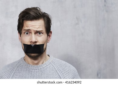 Confused man with tape over mouth, portrait