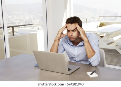 Confused man using laptop on desk at home