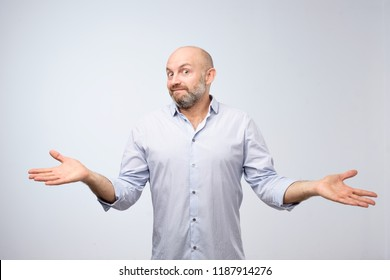 Confused mature bearded man standing and shrugging shoulders isolated over white background. I do not know the solution of this problem concept