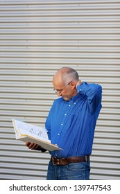 Confused mature businessman reading binder while standing against shutter
