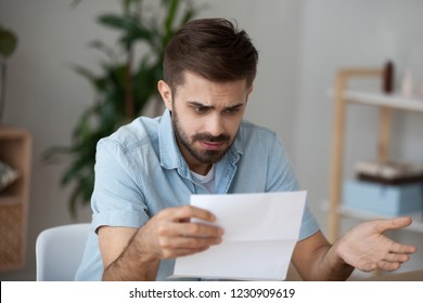 Confused millennial man hold paper document frustrated by read information, puzzled male looking at received letter considering issues, pensive guy pondering over paperwork feel shocked or surprised