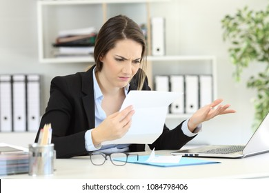 Confused office worker reading documents on a desktop