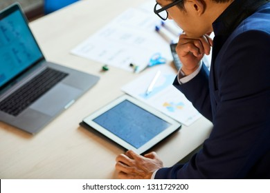 Confused pensive businessman looking at chart on tablet computer in front of him