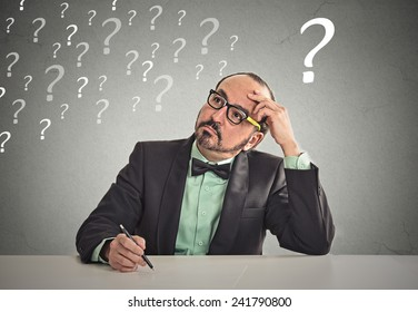 Confused puzzled business man sitting at table scratching his head thinking has many questions isolated office grey wall background. Human face expression emotion feeling body language perception