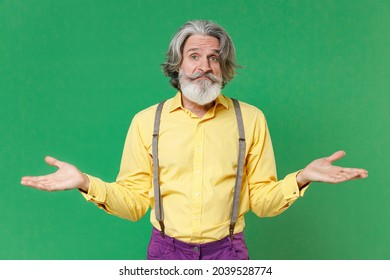Confused puzzled elderly gray-haired mustache bearded man wearing casual yellow shirt suspenders standing spreading hands looking camera isolated on bright green colour background, studio portrait
