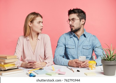 Confused puzzled female and her groupmate look at each other in bewilderment, hold smart phones, search information how to prepare financial report, doesn`t have any idea, need consultation.