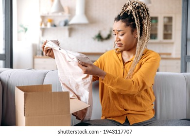 A confused sad african american girl unpacking her parcel at home. Surprised young woman got an unexpected order, girl is upset with her parcel, unsuccessful online shopping. Home delivery