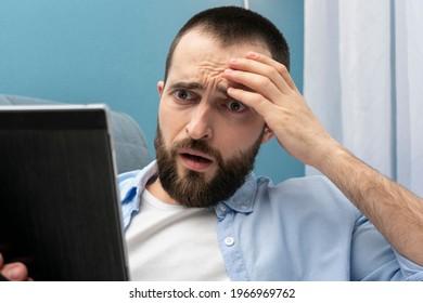 Confused sad bearded man reads e-book, close-up