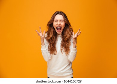 Confused screaming brunette woman in sweater with closed eyes over yellow background