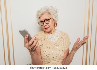 Confused senior woman using mobile phone