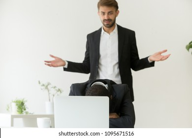 Confused shocked boss observing worker sleeping in front of laptop instead of working, wasting time, being lazy and unmotivated. Concept of misconduct, misbehavior