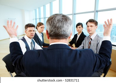 Confused specialists looking at their senior leader with misunderstanding