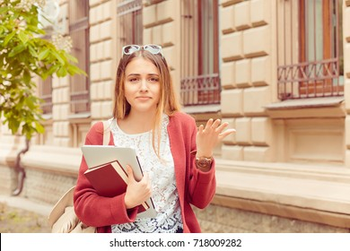 Confused student. Closeup portrait puzzled clueless young woman arm out asking what is problem who cares so what I don't know isolated college building on background. Negative emotion face expression