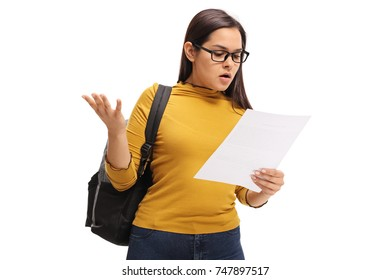 Confused teenage student looking at an exam isolated on white background