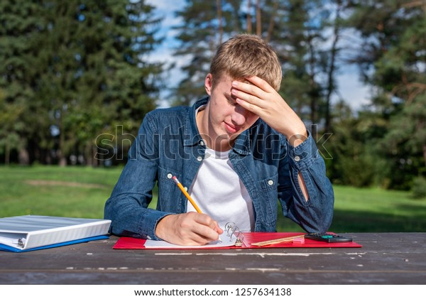 Confused teenager doing his homework alone in a park.