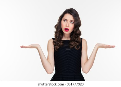Confused thoughtful curly young woman with retro hairstyle and red lips holding copyspace on both palms over white background